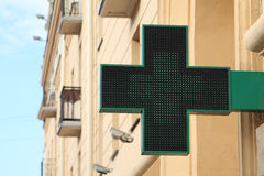 Pharmacy sign on the street. Green pharmacy sign. Stock Photos