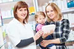 Pharmacy store. Female pharmacist portrait. Pharmacist women worker demonstrating vitamin to child girl with mother in pharmacy drugstore. family health royalty free stock image