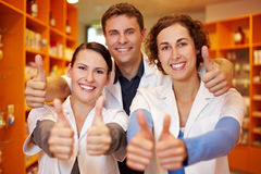 Pharmacy team holding thumbs up royalty free stock photos