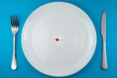 Pharmazeutische Pille oder Kapsel auf einer Platte mit einer Gabel und einem Messer lizenzfreies stockbild