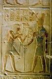 Pharoah Seti presenting lotus flowers to god Horus. An ancient egyptian painted hieroglyphic carving showing the Pharoah Seti presenting sacred lotus flowers to Stock Photos