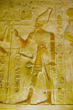 Pharoah Seti with sceptre. A painted Ancient Egyptian hieroglyphic carving showing the Pharoah Seti carrying a ceremonial club or sceptre.  Inner wall of the Royalty Free Stock Images