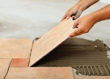 Phasen der Installierung von keramischen Bodenfliesen - Platzierung der Fliese Stockbild