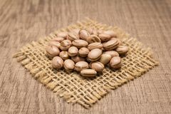 Pinto Bean legume. Grains on square cutout of jute. Wooden table. Phaseolus vulgaris is scientific name of Pinto Bean legume. Also known as Frijol Pinto and Royalty Free Stock Images
