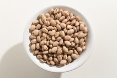 Pinto Bean legume. Top view of grains in a bowl. White backgroun. Phaseolus vulgaris is scientific name of Pinto Bean legume. Also known as Frijol Pinto and Stock Images