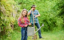 Phases d'aide de lune d?terminer le meilleur jardin d'usine de temps Plantation des fleurs Papa et fille de famille plantant des  images libres de droits