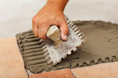 Phases of installing ceramic floor tiles - the adhesive Stock Photos