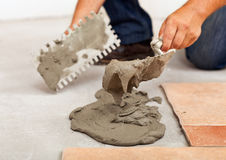 Phases of installing ceramic floor tiles - apply the adhesive Royalty Free Stock Images