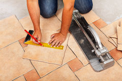 Phases of installing ceramic floor tiles - cutting the pieces Stock Photography