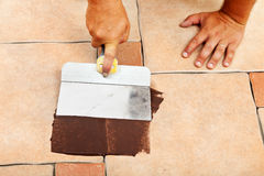 Phases of laying ceramic floor tiles - apply the joint material Stock Image
