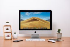 IMac computer, keyboard, magic mouse, plant vase, cactus pots and coffee cup on wooden table royalty free stock photos