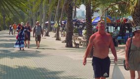 Phatthaya, Thailand - circa January 2018: Boulevard in Phatthaya with palms and people walking along it stock video footage