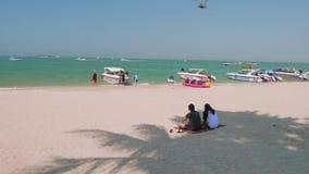 Phatthaya, Thailand - circa January 2018: Tourists sitting on beach and meditating stock video