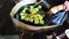 Phayao, Thailand - 2019-03-08 - voedselverkoper roteert vegetarische snack in olie op fornuis stock footage