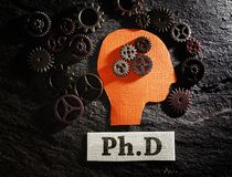 PhD and gears. Head and gears with Ph.D doctorate of philosophy message stock photography
