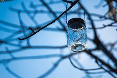 Phetchabun, Thailand - November, 29, 2020 :A glass jar with a small light bulb decorated on the tree, used to decorate at night