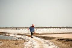 PHETCHABURI,泰国- 2月13 :运载从盐的泰国工作者盐种田2015年2月13日在Phetchaburi,泰国 它是a 免版税库存照片