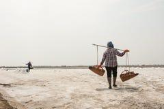 PHETCHABURI,泰国- 2月13 :运载从盐的泰国工作者盐种田2015年2月13日在Phetchaburi,泰国 库存图片