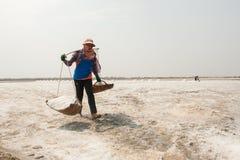 PHETCHABURI,泰国- 2月13 :运载从盐的泰国工作者盐种田2015年2月13日在Phetchaburi,泰国 图库摄影