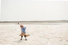 PHETCHABURI, TAILANDIA - 13 DE FEBRERO: Trabajadores tailandeses que llevan la sal de la sal que cultiva el 13 de febrero de 2015 Imagen de archivo libre de regalías