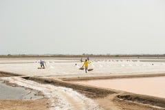 PHETCHABURI, TAILANDIA - 13 DE FEBRERO: Trabajadores tailandeses que llevan la sal de la sal que cultiva el 13 de febrero de 2015 Foto de archivo libre de regalías