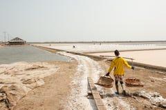 PHETCHABURI, TAILANDIA - 13 FEBBRAIO: Lavoratori tailandesi che portano sale da sale che coltiva il 13 febbraio 2015 in Phetchabu Immagini Stock