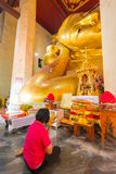 Red shirt woman worshiping reclining golden Buddha image Stock Photography