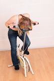 Phew.. Young woman resting on an old exercise bike Royalty Free Stock Photos