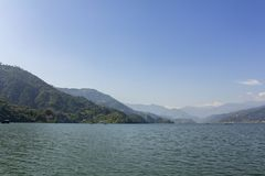 Phewa lake with boats on the background of a green mountain valley under the blue sky, view from the water stock photos