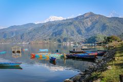Phewa Tal (lake), with boats and Annapurna mountains range, Pokhara, Nepal. Pokhara is a popular destination for trekking in the Annapurna mountains in the Royalty Free Stock Photos