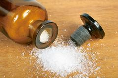 Phial with white powder on the wooden board. Brown glass bottle with spilled white powder Stock Photography