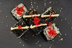 Philadelphia maki roll with mayo and tobiko roe. Philadelphia maki sushi with cream cheese, cucumber and fish. Roll decorated with mayo, red tobiko roe and stock image