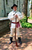 Philadelphia, Pa: Guide Wearing 18th Century Soldier Uniform. A guide wearing colonial-era 18th century soldier's uniform and carrying a long rifle at the Second Stock Image