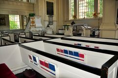 Philadelphia, PA: Pews at Christ Church. Philadelphia, Pennsylvania: White boxed wooden pews with red and blue prayer hymnals fill the interior of historic 1727 stock photo