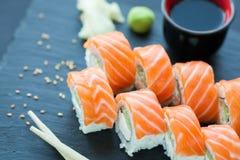 Philadelphia roll classic on a dark stone background. Salmon, Philadelphia cheese, cucumber, avocado. Japanese sushi. Royalty Free Stock Photos