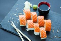 Philadelphia roll classic on a dark stone background. Salmon, Philadelphia cheese, cucumber, avocado. Japanese sushi. Stock Photos