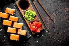 Philadelphia roll sushi with salmon, shrimp, avocado and cream cheese. On dark rustic background stock images