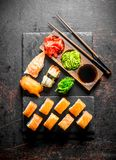 Philadelphia roll and various sushi with sauce on a stone Board. On dark rustic background stock images