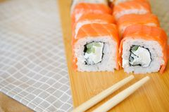 Cream rolls with salmon lie on a wooden plank royalty free stock photo