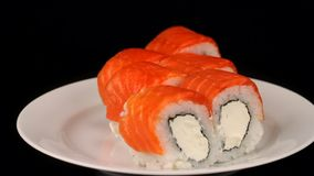 Philadelphia rolls are rotating on a plate, Japanese cuisine on black background. Full HD stock video