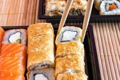 Philadelphia rullsushi med laxen och rulle i omelettet Sushimeny Japansk mat Royaltyfri Bild