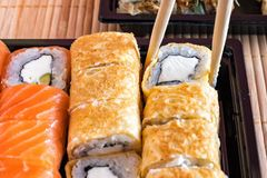 Philadelphia rullsushi med laxen och rulle i omelettet Sushimeny Japansk mat Arkivfoton