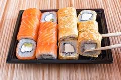 Philadelphia rullsushi med laxen, tonfisk, avokadot, gräddost och rulle i omelettet Sushimeny Japansk mat Fotografering för Bildbyråer