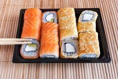 Philadelphia rullsushi med laxen, tonfisk, avokadot, gräddost och rulle i omelettet Sushimeny Japansk mat Royaltyfri Fotografi
