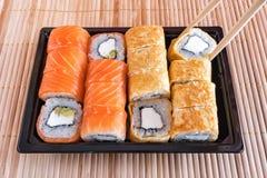 Philadelphia rullsushi med laxen, tonfisk, avokadot, gräddost och rulle i omelettet Sushimeny Japansk mat Arkivfoto