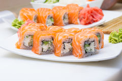 Philadelphia sushi roll with ginger and wasabi on white plate Royalty Free Stock Photography