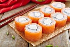 Philadelphia Sushi Rolls. Beautiful Philadelphia Sushi Rolls Set with Salmon and Cream Cheese on Wooden Rustic Background Close Up. Uramaki, Nori Maki or royalty free stock image