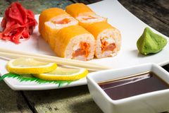 Philadelphia sushi rolls on white plate with chopstick and wasabi Stock Images