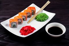 Philadelphia sushi rolls on a white square plate with wasabi, soy sauce and ginger. Dark wooden background.  royalty free stock images