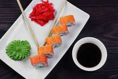Philadelphia sushi rolls on a white square plate with wasabi, soy sauce and ginger. Dark wooden background.  stock photo